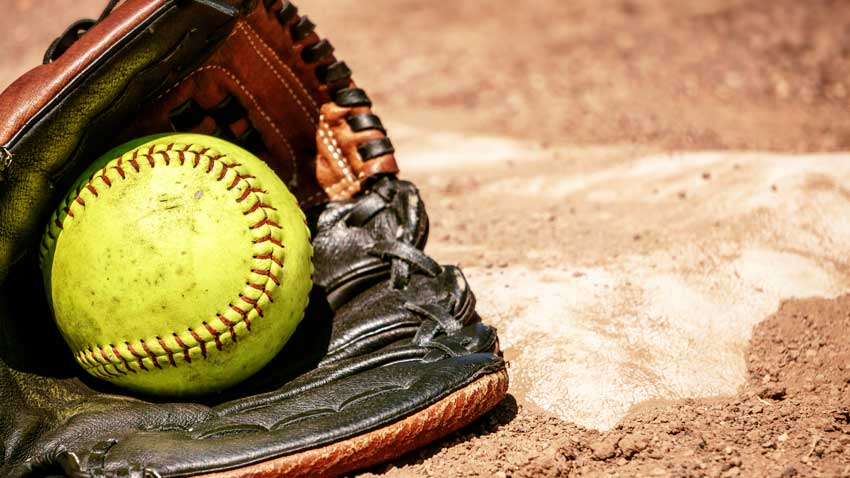 Softball in a glove at home plate
